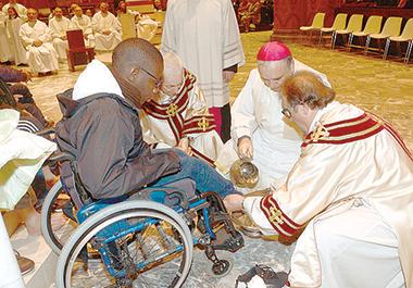 Monsignor Marco Brunetti, Vescovo di Alba, alla lavanda dei piedi. Foto Marcato
